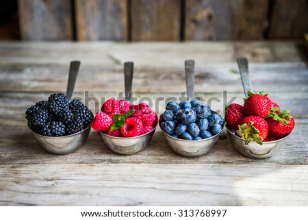 Mix of fresh berries on rustic background - stock photo