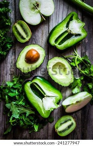 Mix of green vegetables and fruits on rustic background - stock photo
