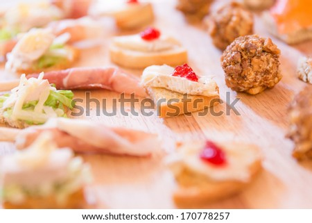 Mix of Hors D'oeuvres on a wooden platter - stock photo