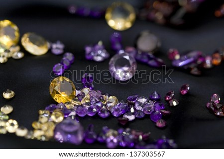 Mix of natural and colorful gems on the black background - stock photo
