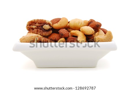 Mix of nuts close up in plate on white - stock photo