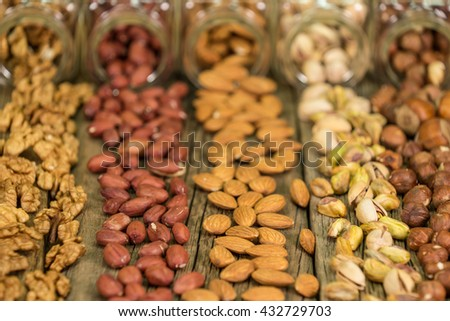 Mix of nuts in the glass jars , on the table, selective focus - stock photo