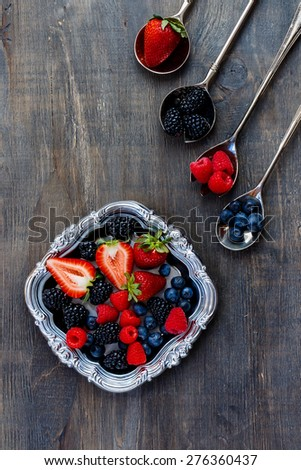 Mix of organic berries on vintage metal plate over dark wooden background. Agriculture, Gardening, Harvest Concept. - stock photo