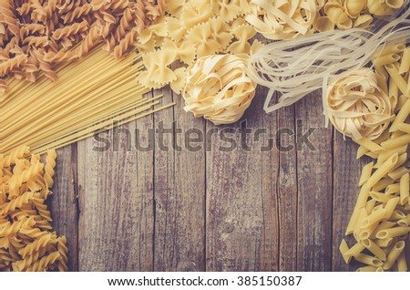 Mix of pasta on an old wooden table - stock photo
