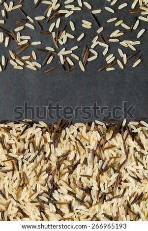 Mix of rice on a black chalkboard background - stock photo