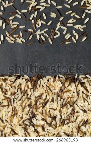 Mix of rice on a black chalkboard background - stock photo