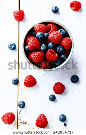 Mix of ripe berries in bowl on white wooden background. Top view. - stock photo