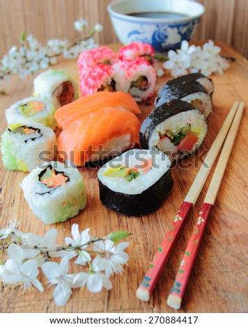 Mix of sushi rolls on wooden desk with chopsticks - stock photo