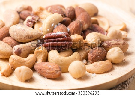 mix of various nuts on wooden background - stock photo