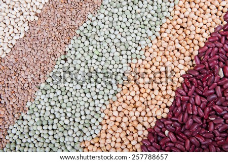mix of various raw legumes on wooden table, with white beans, kidney beans, lentils, green peas, chickpeas - stock photo