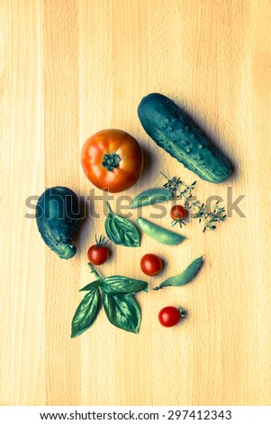 Mix of vegetables on wooden background - summer garden harvest. Cucumbers, tomatoes, pea and herbs. Retro filter. - stock photo