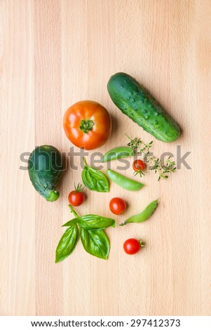 Mix of vegetables on wooden background - summer garden harvest. Cucumbers, tomatoes, pea and herbs. - stock photo