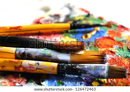 Mix of vivid paints and paintbrushes - stock photo