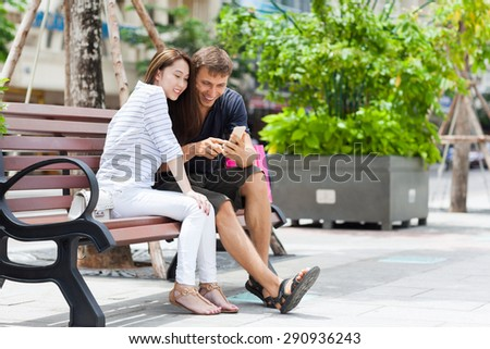 Mix race couple using cell smart phone sitting in bench smile, asian girl and caucasian man city street - stock photo
