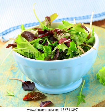 mix salad (arugula, iceberg, red beet) in a bowl - stock photo