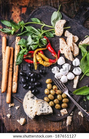 Mixed antipasti bread sticks, olives and mozzarella served on cast-iron board over wooden table with vintage fork. Top view. - stock photo
