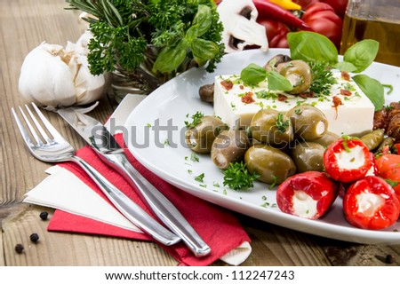 Mixed Antipasto on a plate against wood - stock photo