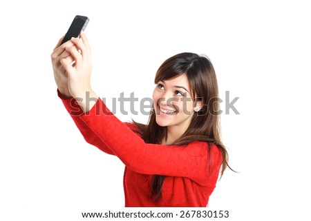 Mixed Asian girl taking a selfie with her phone on white background - stock photo