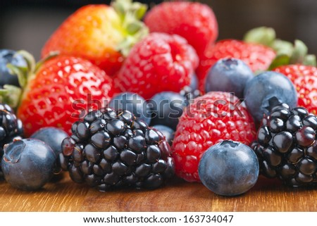 Mixed berries on a wooden background with selected focus.Strawberries, Raspberries Blackberries and Blueberries. Healthy Living and Nutritious Food concept. - stock photo