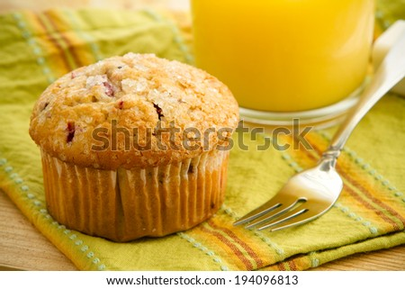 Mixed Berry Muffin - This is a shot of a delicious mixed berry muffin shot on a cedar tabletop with a table cloth next to a glass of juice. Shot with a shallow depth of field. - stock photo