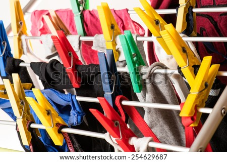 mixed  clean laundry pinned with colourful clothespins on white background - stock photo