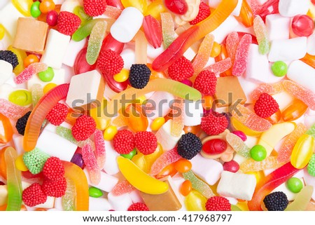 Mixed colorful candies, jellies and marshmallows as background - stock photo