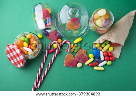 Mixed colorful fruit candies and jellies on green background - stock photo