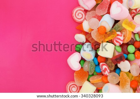 Mixed colorful fruit candies and jellies on pink background with room for text - stock photo
