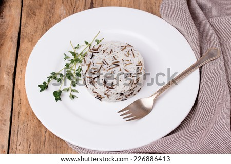 Mixed cooked rice with thyme and fork on white plate on wooden table. Basmati and wild rice mix. - stock photo