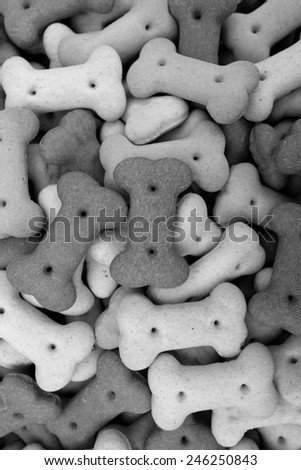 Mixed dog biscuits as a vertical abstract background texture - monochrome processing - stock photo