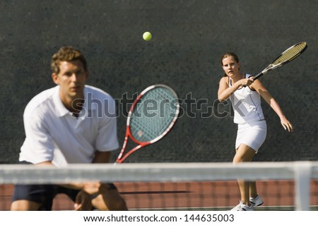 Mixed doubles player hitting tennis ball with partner standing near net - stock photo
