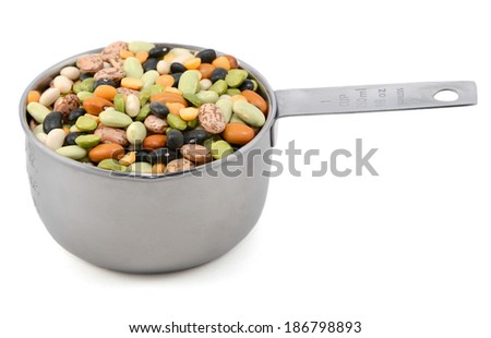 Mixed dried beans - black turtle beans, flageolet beans, pinto beans, brown beans, haricot beans, green split peas and yellow split peas - in a metal cup measure, isolated on a white background - stock photo