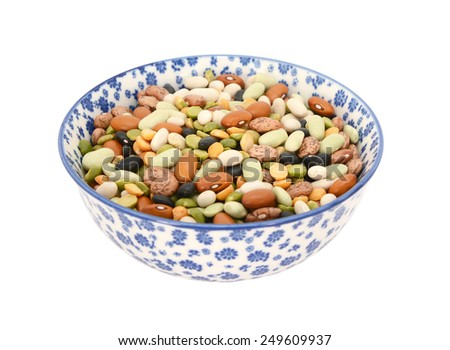 Mixed dried beans - black turtle beans, flageolet beans, pinto beans, brown beans, haricot beans and split peas -  in a blue / white porcelain bowl with a floral design, isolated on a white background - stock photo