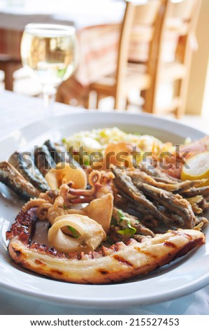 Mixed fish food on the plate and white wine - stock photo