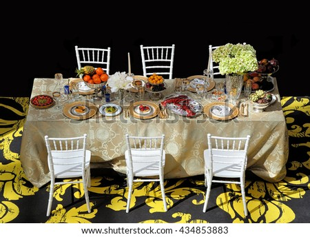 Mixed food on a table and six chairs - stock photo