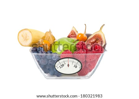 Mixed fresh fruit in glass bowl with weight scale for diet concept on white background.  - stock photo