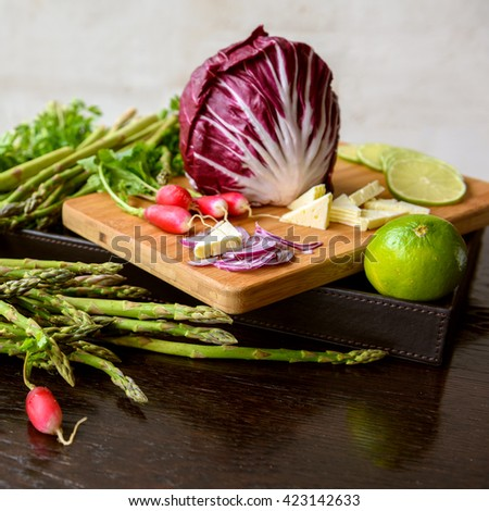 Mixed fresh spring vegetables: asparagus, radish, herbs, lime, cheese, mozzarella on a wooden table and cutting desk - stock photo