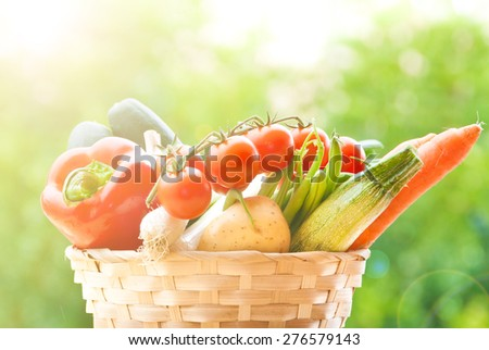 Mixed fresh vegetables in a basket on table - stock photo