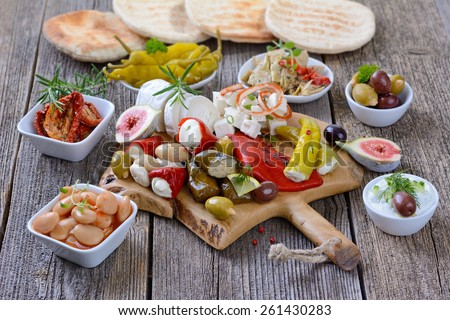 Mixed Greek antipasti on a wooden cutting board - stock photo