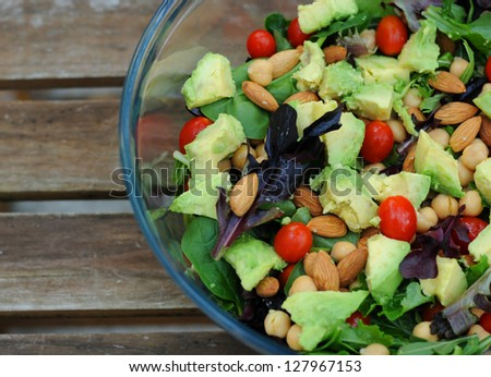 Mixed green salad with vegetables and nuts - stock photo