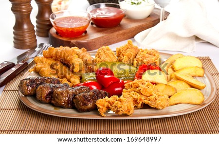 Mixed grilled and fried  meat platter and pickles - stock photo
