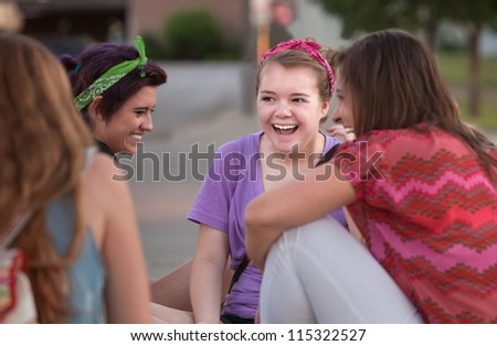 Mixed group of four teenage girls outside giggling - stock photo