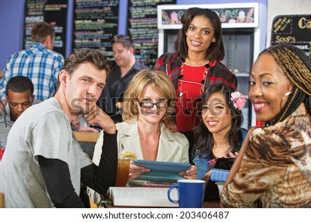 Mixed group of students with tablet computer in cafe - stock photo