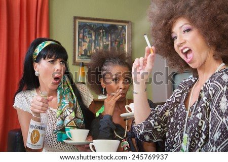 Mixed group of 3 women smoking and drinking alcohol - stock photo
