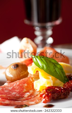 mixed italian antipasti on a plate with wine  - stock photo