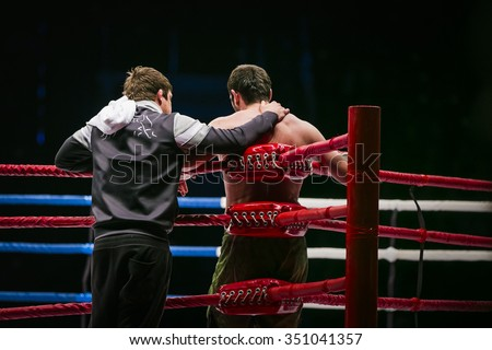 mixed martial arts fighter (MMA) stands in corner ring next to him coach. break between rounds in fight - stock photo