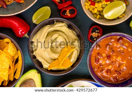 Mixed mexican food. Party food. Guacamole, nachos, fajita, meat tacos, salsa, peppers, tomatoes on a wooden table. Top view. Tex-mex cuisine. Assorted appetizers. Cuisine of Mexico - stock photo