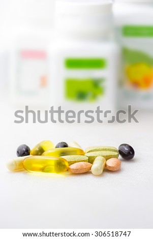 Mixed natural food supplement pills such as  fish oil capsules, vitamin pills , carotene capsules, close-up on white background - stock photo