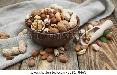 Mixed nuts in a bowl on a wooden background  - stock photo