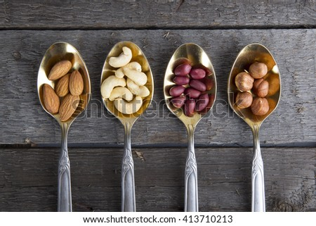Mixed nuts in metal spoon on wooden table. Rustic style. - stock photo